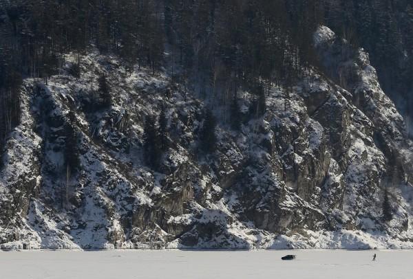 Мужчина катается на сноуборде по замерзшей реке Енисей. Фото: Ilya Naymushin / Reuters