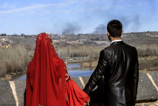 Молодожены фотографируются на фоне района Сур. Фото: Ilyas Akengin / AFP / EastNews
